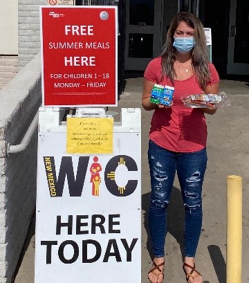 Pictured: New Mexico WIC staff member offering WIC service and free summer meals at WIC's curbside clinic.