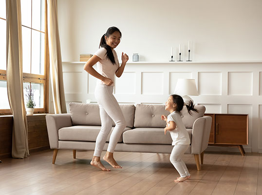 Mother and daughter dancing at home