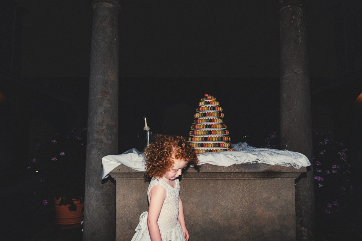 Wedding photographer in Umbria, Agriturismo I Frati Paciano, Italian wedding, Ayesha Photography, Destination wedding photography, Italy wedding photographer, Tuscany wedding photographer, Manchester wedding photographer, flower girl looks sad next to wedding cake