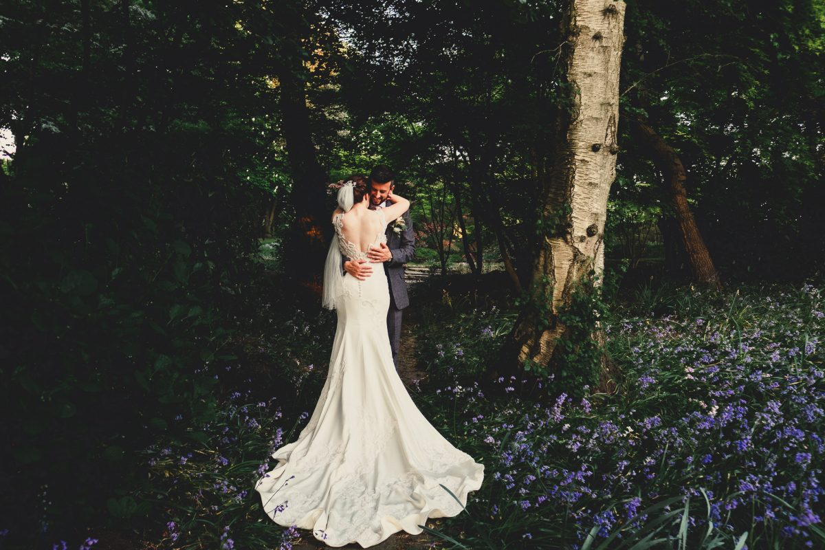colshaw hall wedding photography, ayesha photography, manchester wedding photographer, manchester wedding photographer, cheshire wedding photographer, cheshire wedding photography, bride and groom hug in bluebell field and you can see the back of her dress