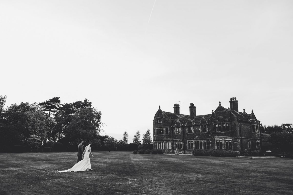 colshaw hall wedding photography, ayesha photography, manchester wedding photographer, manchester wedding photographer, cheshire wedding photographer, cheshire wedding photography, black and white photo of bride and groom walking in front of colshaw hall
