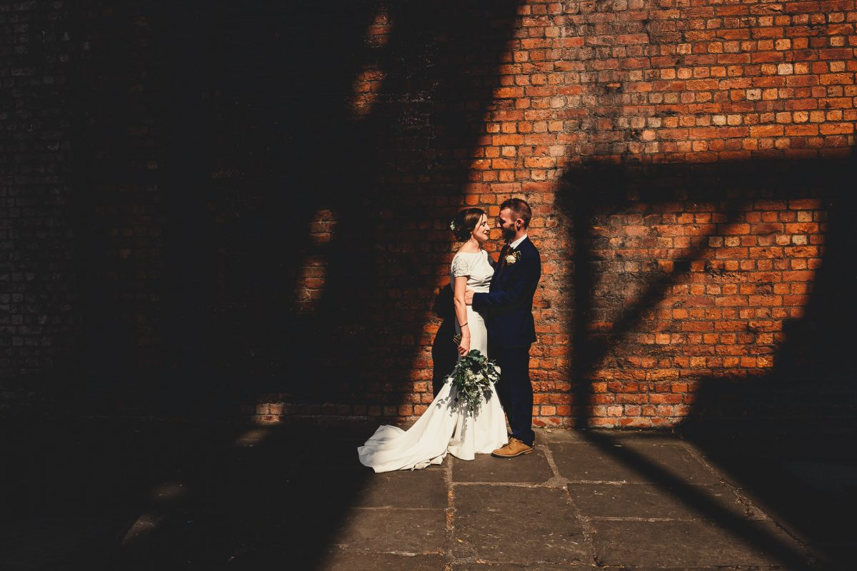 castlefield rooms wedding photographer, castlefield rooms wedding photography, manchester wedding photographer, manchester wedding photography, manchester city centre wedding, ayesha photography, creative manchester wedding photographer, destination wedding photographer, ibiza wedding photographer, ibiza wedding photography, italy wedding photographer, mallorca wedding photographer, bride and groom stand in the light near a brick wall