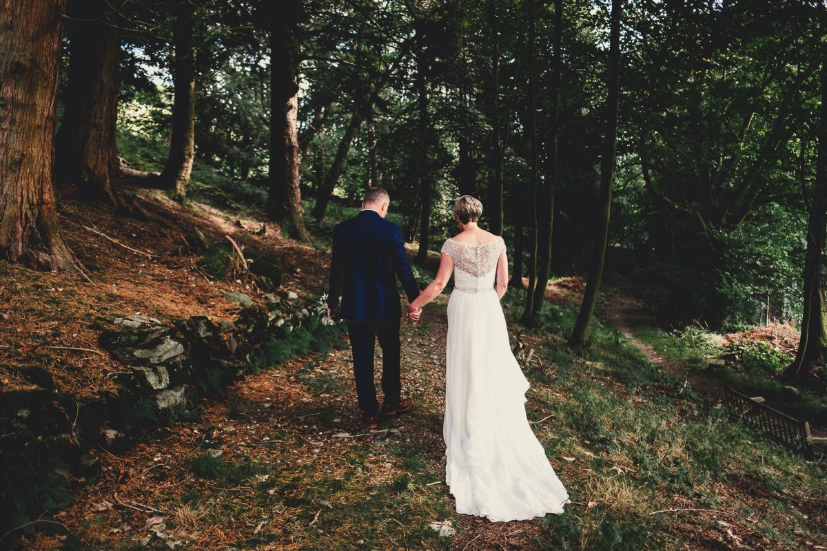forest side wedding photographer, forest side wedding photography, lake district wedding, lake district wedding photographer, lake district wedding photography, grasser wedding photographer, grasmere wedding photography, ayesha photography, forest wedding photography, manchester wedding photographer, manchester wedding photography, bride and groom walk hand in hand through the forest