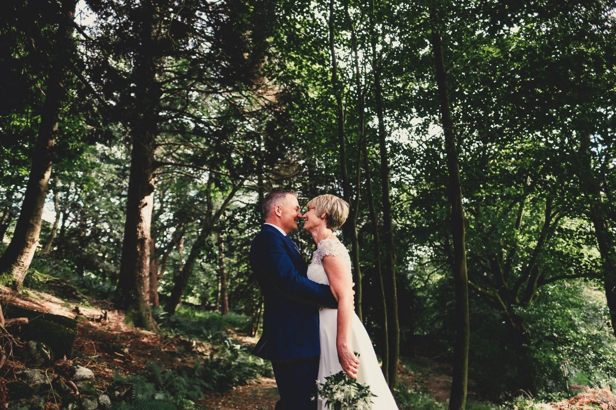 forest side wedding photographer, forest side wedding photography, lake district wedding, lake district wedding photographer, lake district wedding photography, grasser wedding photographer, grasmere wedding photography, ayesha photography, forest wedding photography, manchester wedding photographer, manchester wedding photography, bride and groom look at each other whilst stood in the forest