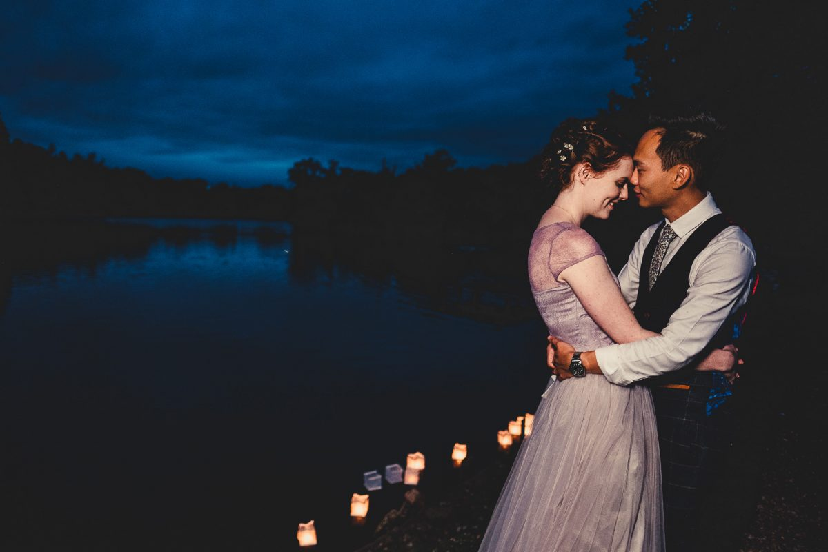 manchester wedding photographer, manchester wedding photography, cheshire wedding photographer, cheshire wedding photography, norcliffe chapel wedding photography, styal wedding photographer, roman lakes wedding photographer, roman lakes wedding photography, ayesha photography, creative manchester wedding photographer, bride and groom hold each other by the lake at dusk with floating candles on the lake