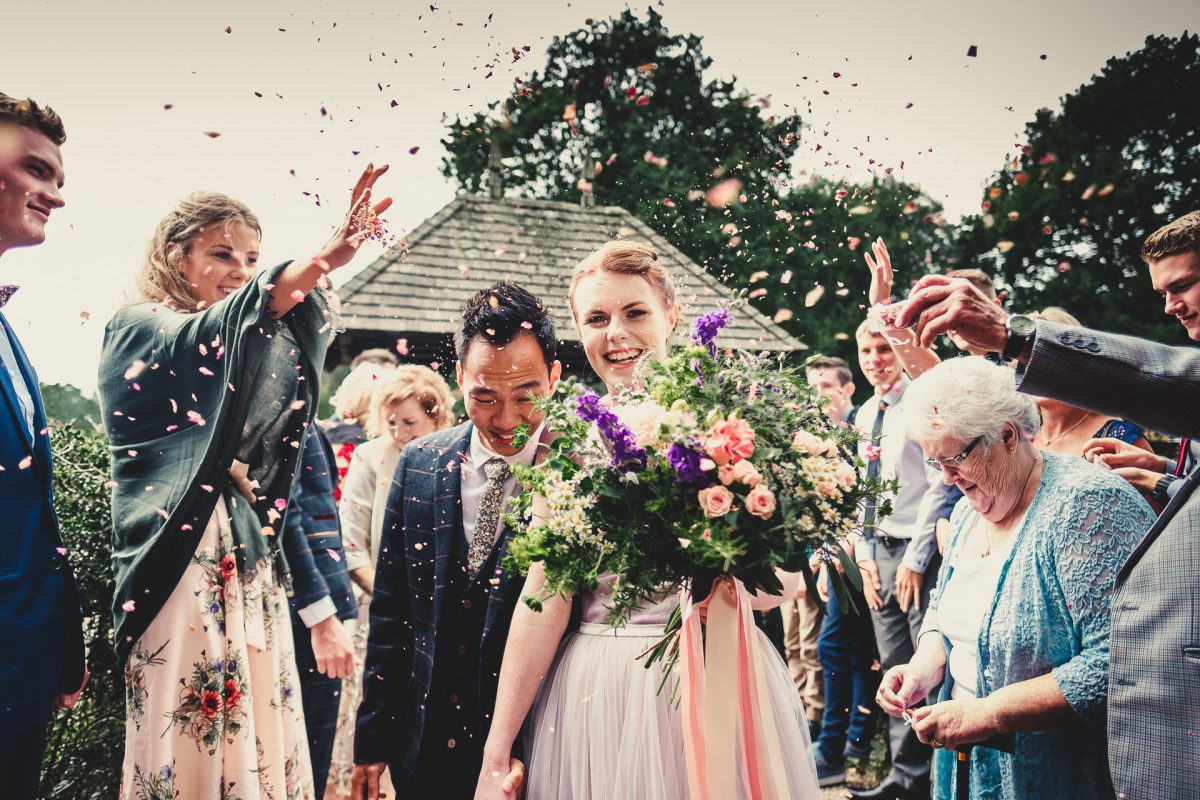 manchester wedding photographer, manchester wedding photography, cheshire wedding photographer, cheshire wedding photography, norcliffe chapel wedding photography, styal wedding photographer, roman lakes wedding photographer, roman lakes wedding photography, ayesha photography, creative manchester wedding photographer, bride and groom walk out through a confetti tunnel outside norcliffe chapel