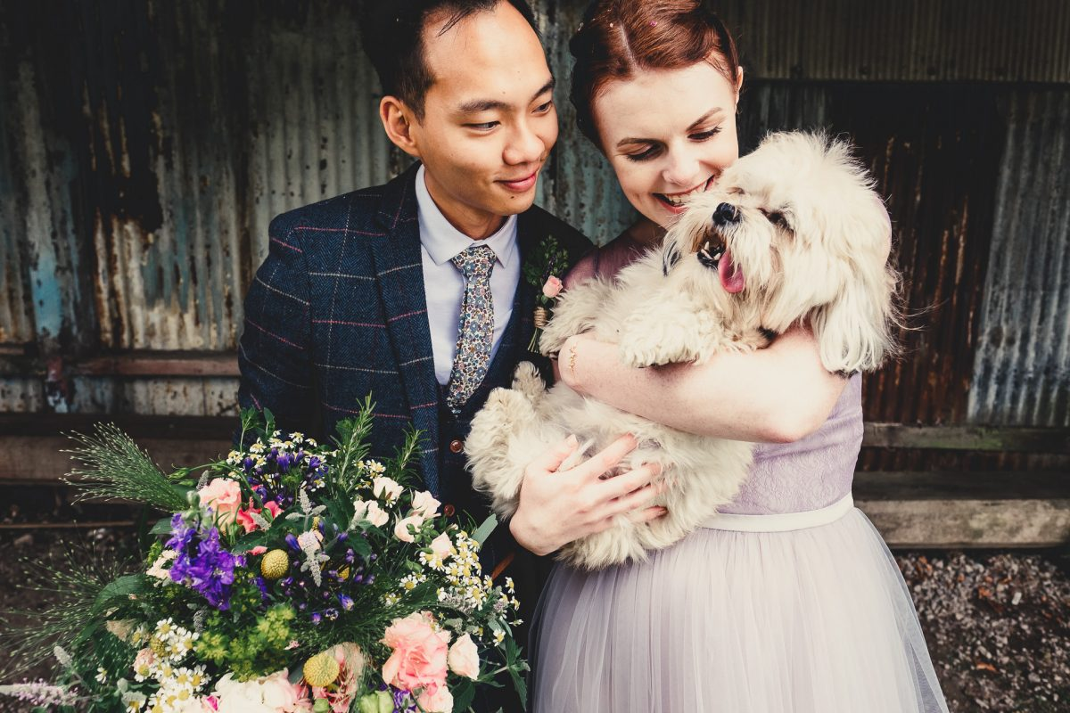 manchester wedding photographer, manchester wedding photography, cheshire wedding photographer, cheshire wedding photography, norcliffe chapel wedding photography, styal wedding photographer, roman lakes wedding photographer, roman lakes wedding photography, ayesha photography, creative manchester wedding photographer, bride and groom hold their dog and bride gives dog a tickle whilst holding flowers