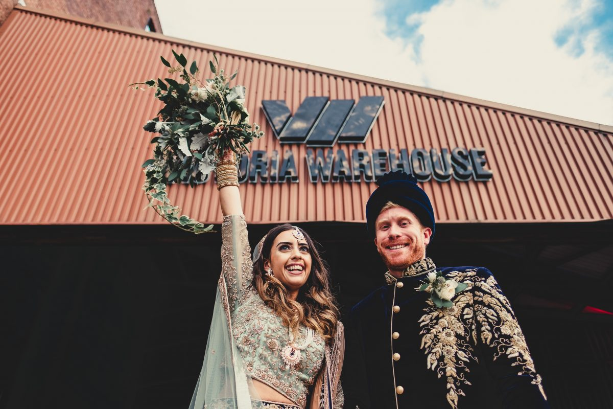 VICTORIA WAREHOUSE ASIAN WEDDING PHOTOGRAPHY, MANCHESTER WEDDING PHOTOGRAPHER, MANCHESTER WEDDING PHOTOGRAPHY, VICTORIA WAREHOUSE WEDDING PHOTOGRAPHER, VICTORIA WAREHOUSE WEDDING, ASIAN WEDDING PHOTOGRAPHER, MANCHESTER ASIAN WEDDING PHOTOGRAPHER, ASIAN FUSION WEDDING PHOTOGRAPHY, AYESHA PHOTOGRAPHY, BRIDE HOLDS UP HER WEDDING FLOWERS WITH THE GROOM OUTSIDE VICTORIA WAREHOUSE