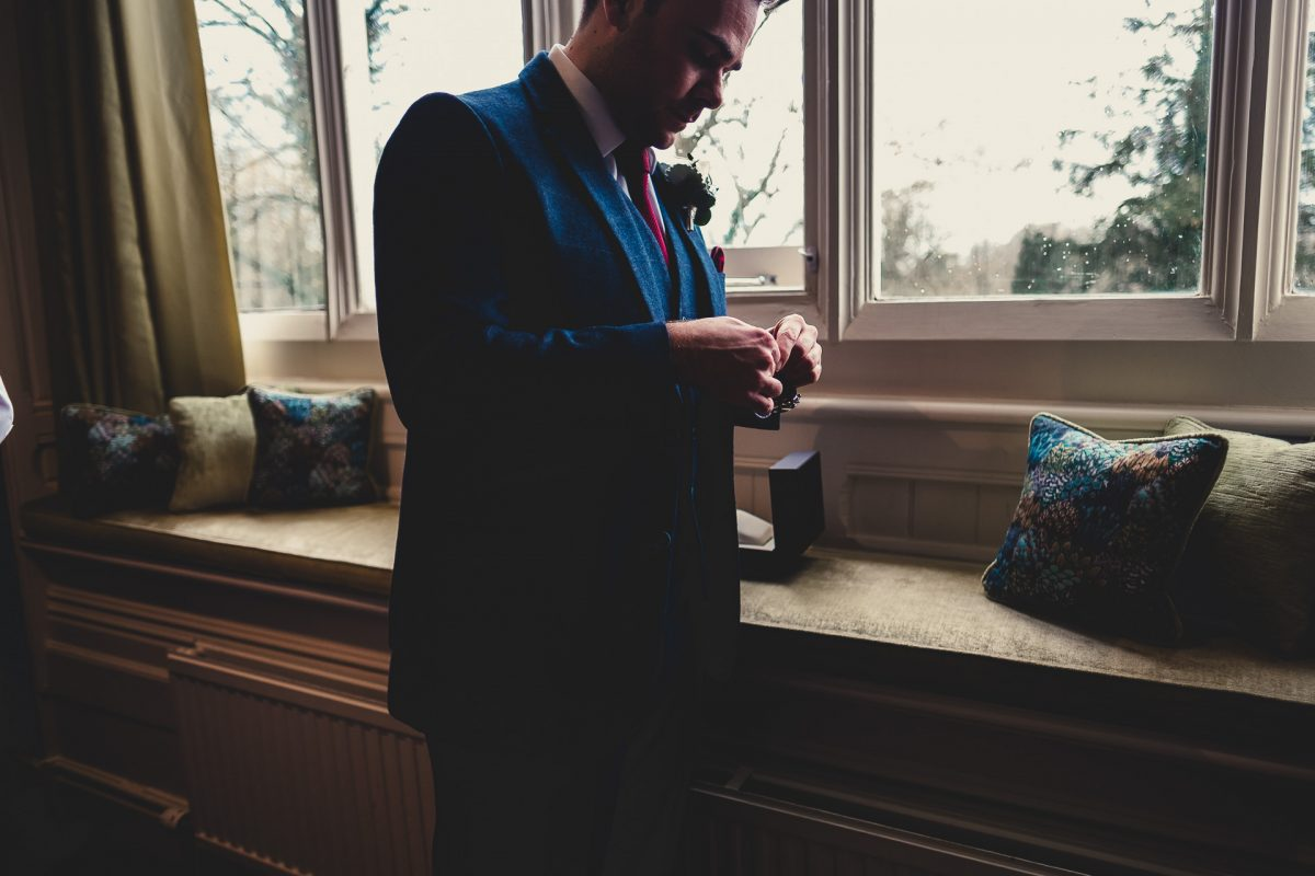 mitton hall wedding photography, mitton hall wedding photographer, mitton hall, mitton hall wedding, lancashire wedding photographer, lancashire wedding photography, manchester wedding photographer, manchester wedding photography, ayesha photography, groom putting his watch on stood next to a window