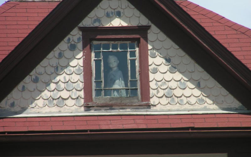 The Janesville Doll sits in the window of an old home, overlooking the community.