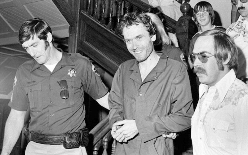 A handcuffed Ted Bundy is escorted down the stairs.