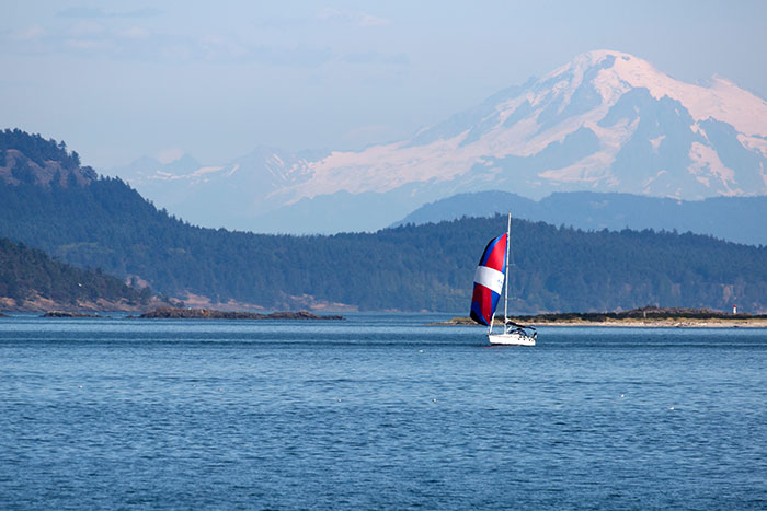 Snow-capped Mountains and a Sailboat in the BC Gulf Island Waters, Canada