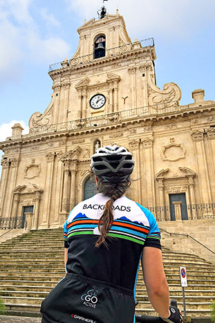 Backroad cyclist at the Church Of San Sebastiano In Palazzolo Acreide, Siracusa, Sicily, Italy