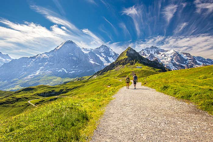 Trail leading to Kleine Scheidegg from Mannlichen with Eiger, Monch and Jungfrau mountain behind, Switzerland
