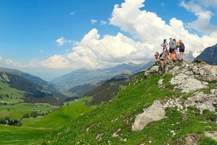 Family resting atop a Swiss Alps hill after a hike
