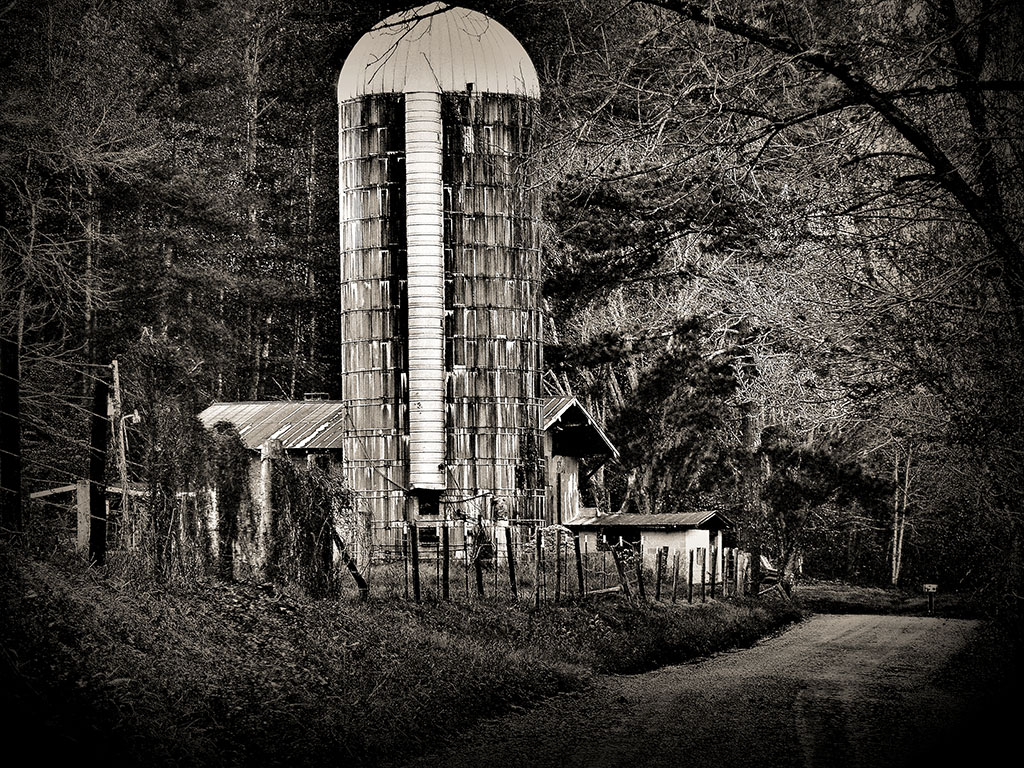 Black and white art featuring barn and grain silo