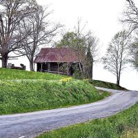 Farmhouse style art featuring a black barn at the curve of a country road
