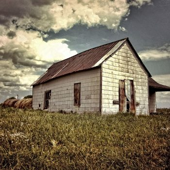 Product, Rustic Canvas Wall Art: Sunny Day - Abandoned white building in field with stormy skies and hay bales