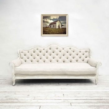 Rustic canvas wall art featuring white building and blue skies above white couch