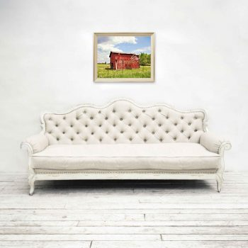 Art with colorful red barn with purple spring tree on wall above white couch