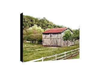 Living room canvas wall decor featuring wooden barn with cross on the side behind white farm fence