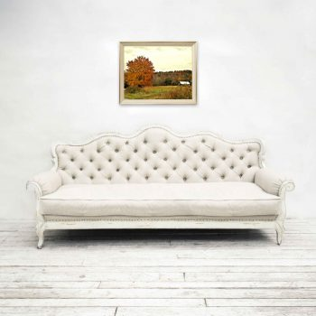 Autumn foliage and barn wall decor hung in home over white couch
