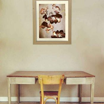 Beige wall with wall art featuring brown flowers hung over old fashioned wooden desk