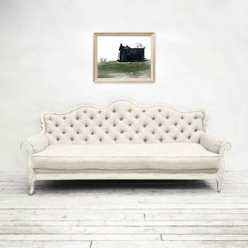 Picture of black country barn on green hill above a white couch