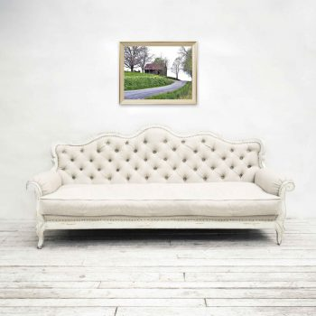 Art featuring black barn at top of hill hung above white couch