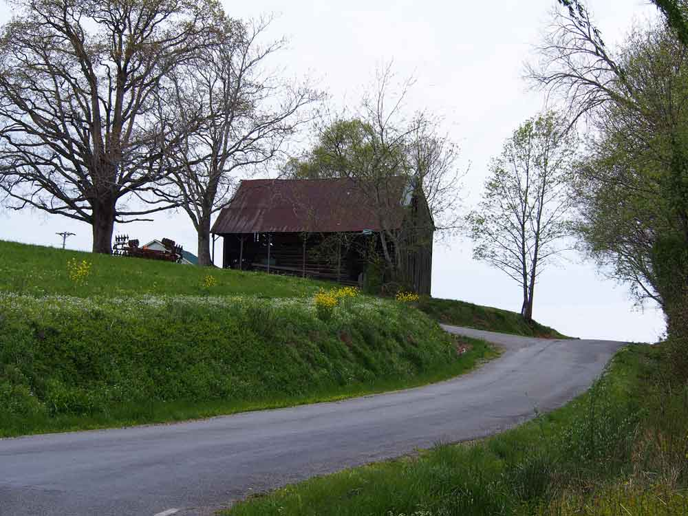 Original image of old black barn next to country road