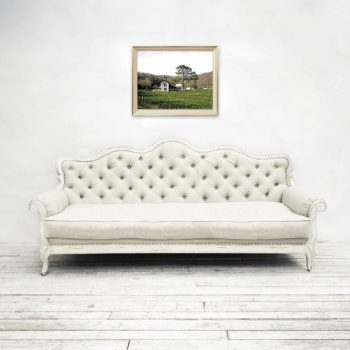 Old farmhouse on wall above white couch
