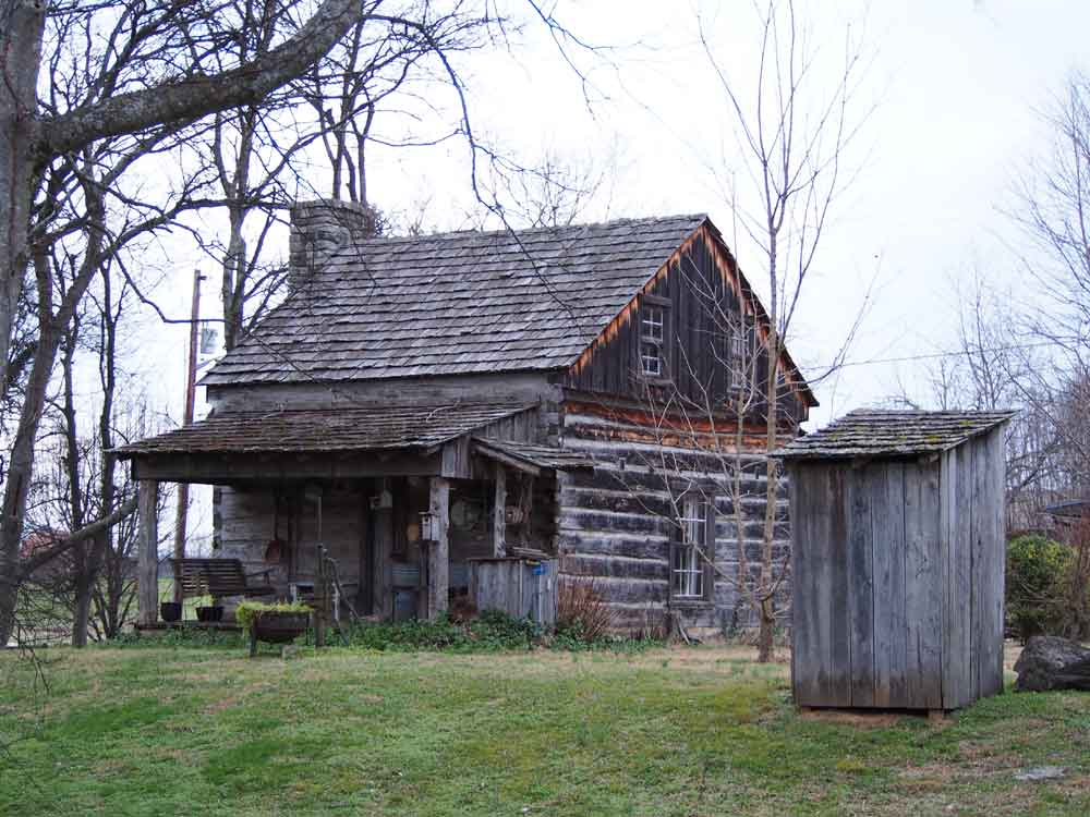 Original image of rustic log cabin and outhouse
