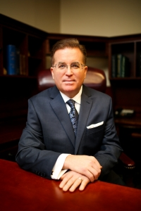 A waist-up shot of a man sitting at a table, in front of bookcases. He has short brown hair and eyeglasses and wears a navy blue suit. He is looking neutrally at the viewer.