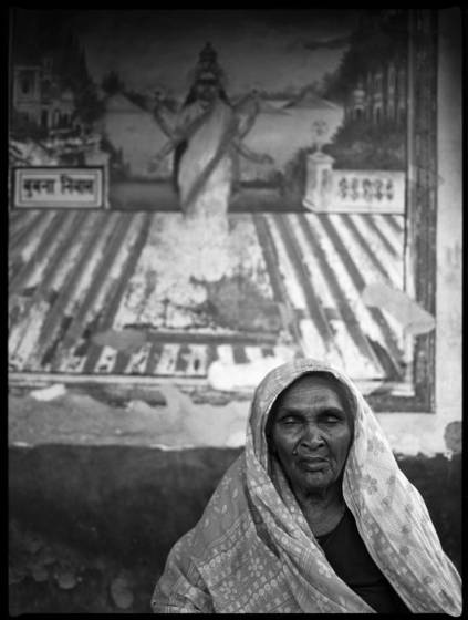 Old woman in front of mural