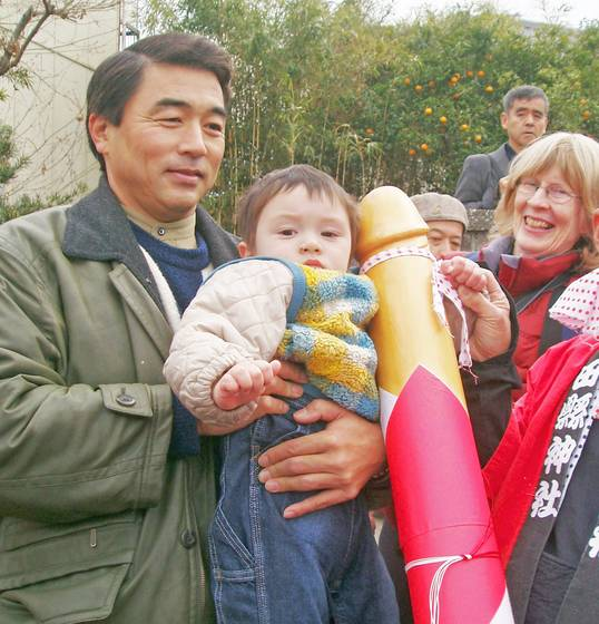 Father and son with wooden phallus at honen sai festival
