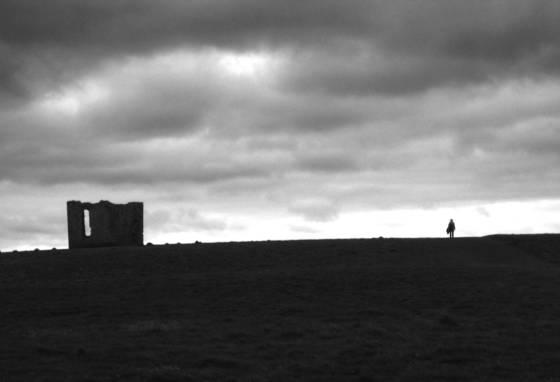 Man walking by a ruin