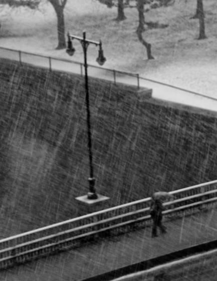Snow falling on a man crossing a bridge