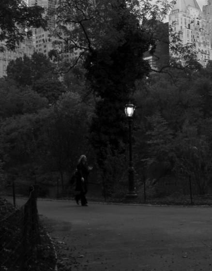 Woman walking at dusk in central park