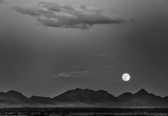 Full moon over desert mountains