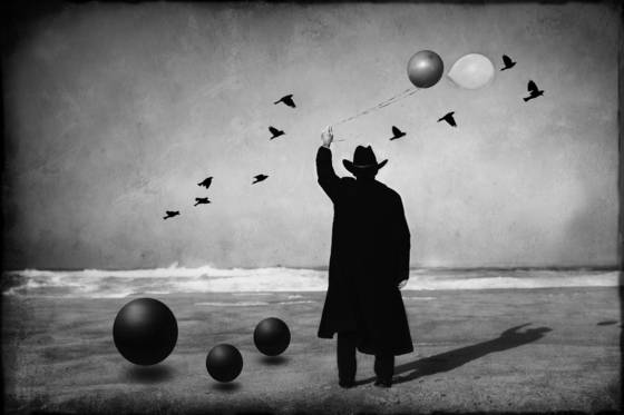 Man in black with balloons birds and sphere