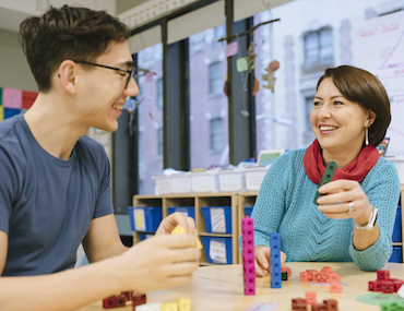 Two educators using math cubes at table
