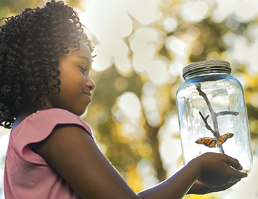Girl looking at butterfly in jar