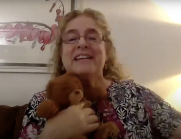 Lesley Koplow holding a teddy bear during Emotionally Responsive Schools Conference keynote presentation 2020