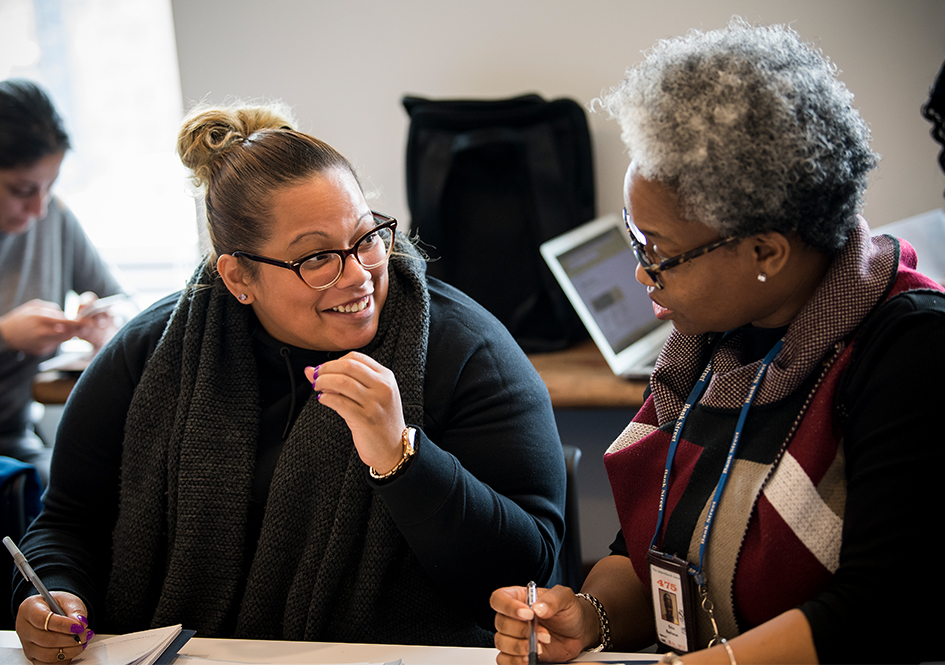 Two educators talking together at a table