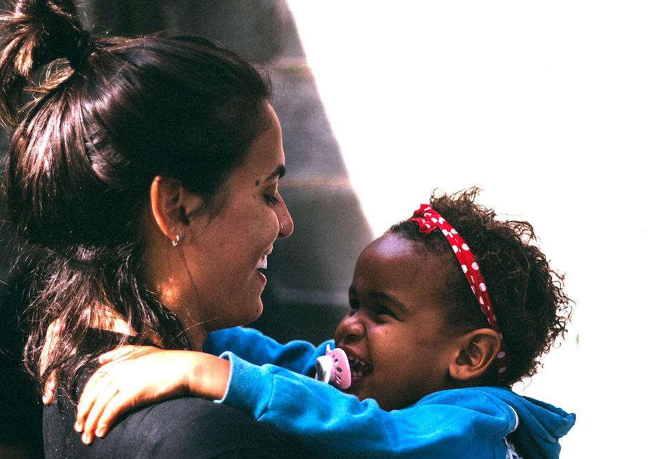 Toddler smiling and hugging teacher