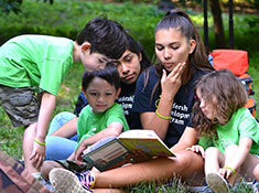 Older camp counselor reads to young campers