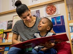 Teacher and young child reading in library