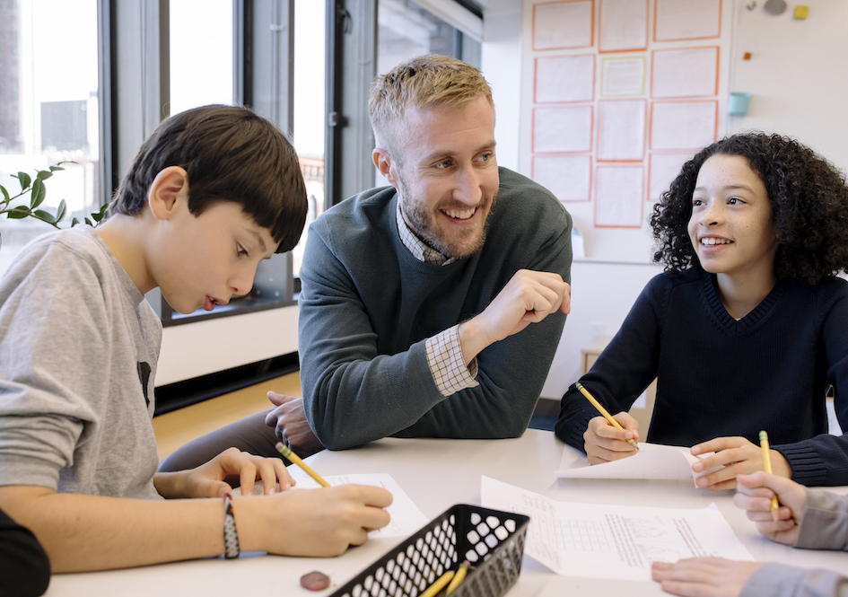 Two students writing at table with teacher