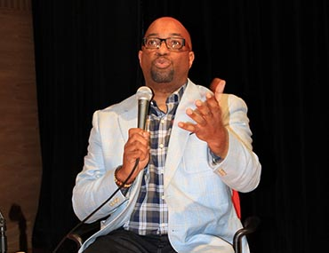 Kwame Alexander speaks on stage in a panel
