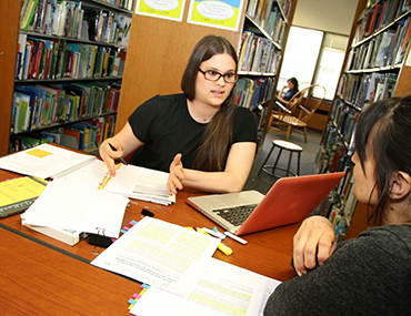 Graduate students sit at desk in library